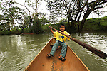 A Mayan boy paddles his dugout canoe on a jungle river near his village, Crique Sarco, in southern Belize.