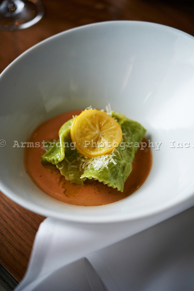A bowl of agnolotti (ravioli typical of the Piedmont region of Italy) filled with crab, topped with lemon slice. On location at a restaurant.