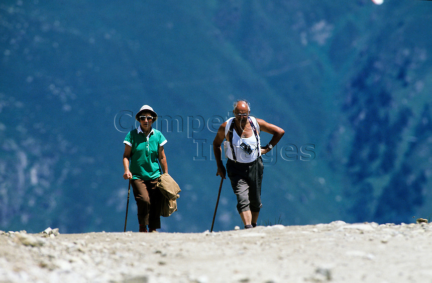 Man and woman walking along a gravel mountain path