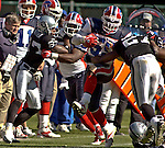 Oakland Raiders running back J.R. Redmond (27) tackles Buffalo Bills linebacker London Fletcher (59) after loose ball on Sunday, September 19, 2004, in Oakland, California. The Raiders defeated the Bills 13-10.