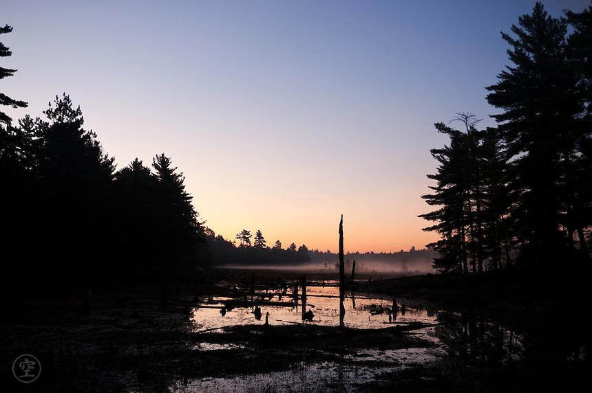 Daybreak. Mist rises from the lake as the sky lightens.
