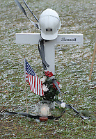 A miner's helmet sits atop the cross for Sago miner Alva Marty Bennett at the memorial on the county courthouse lawn in Phillipi, WV Friday, Jan. 6, 2006. Bennett is one of the 12 miners killed in the Sago mine explosion. (Gary Gardiner/EyePush Newsphotos)<br />