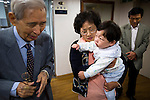 During a teary moment of international transition, foster mother and father Oh prepare to hand off 15-month-old Cho, Hyeon Bhin to awaiting adoptive parents, Jeff Miller and Suzanne Stute, at the Eastern Social Welfare Society (ESWS) in Seoul, South Korea on Oct. 8, 2008, At left, ESWS director Dr. Kim prays for health and happiness of the boy, later renamed Holden Hyeon Bhin Miller, and his new family.