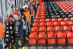 Dundee United fans making their way out of the stadium after their team's Scottish Premier League match at Tannadice Park, Dundee against visitors Dunfermline Athletic. The visitors won the game by one goal to nil, watched by a crowd of 6,527. Dundee United's stadium was situated on the same street as their city rival Dundee, whose Dens Park ground was visible in the background.