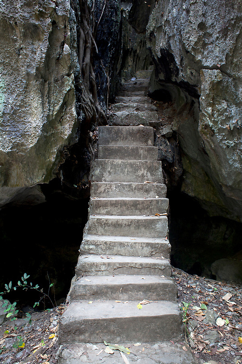 Stairway into a network of caves with buddhist statues outside the resort town of Kep, Cambodia. <br /> <br /> Photos &copy; Dennis Drenner 2013.