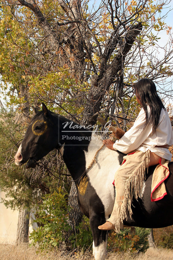 A Native American Indian man sitting on a war painted horse and using a war bridle