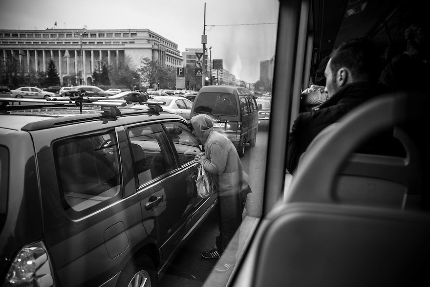 A homeless youth begging for money in traffic stopped at Piata Victoriei in central Bucharest.