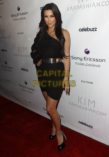 KIM KARDASHIAN.Sony Ericsson and Celebuzz Celebrate KimKardashian.com held at The Tea Room,  Hollywood, CA, USA, .25th June 2010..full length one sleeve dress black hand on hip waist belt silver shoes .CAP/ADM/KB.©Kevan Brooks/AdMedia/Capital Pictures.