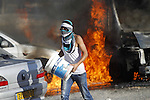 A masked Palestinian youth tries to extinguish the fire in cars during clashes with Israeli security forces after Moataz Higazi was shot in east Jerusalem October 30, 2014. Israeli police shot and killed Higazi suspected of trying to kill a hard-line Jewish activist in Jerusalem, an incident that quickly sparked clashes between masked stone throwers and Israeli riot police, threatening to further enflame the already high tensions in the city. Photo by Muammar Awad