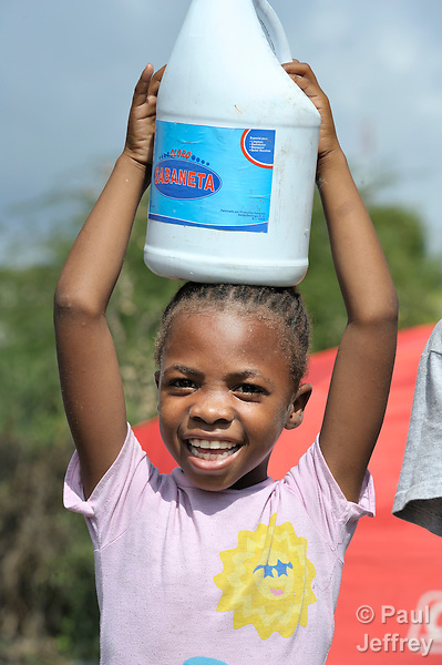 A girl living in a camp for homeless families helps unload bleach, part of an emergency shipment of relief supplies delivered to quake survivors in Jacmel, a town on Haiti's southern coast that was ravaged by the January 12 earthquake.