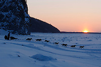 Friday March 12 , 2010   Dallas Seavey drops down the bank onto the Yukon River shortly after leaving the village checkpoint of Ruby at sunset .