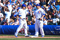 Chicago Cubs pinch hitter Chris Valaika (4) fist bumps Eric Hinske (2) after reaching first during a game against the Milwaukee Brewers on August 14, 2014 at Wrigley Field in Chicago, Illinois.  Milwaukee defeated Chicago 6-2.  (Mike Janes/Four Seam Images)
