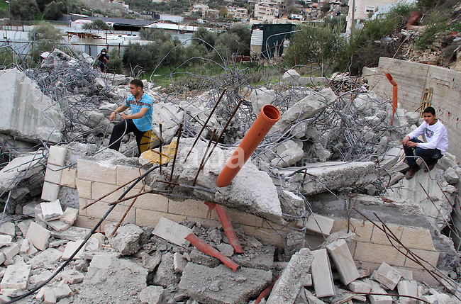 Palestinians inspect their house that was demolished by Jerusalem municipality workers on Jerusalem in Jan. 07, 2016. Israeli police Thursday demolished two Palestinian-owned homes in Ein el-Lawza neighborhood in Jerusalem, citing construction without a permit as a pretext, according to local sources. Photo by Mahfouz Abu Turk