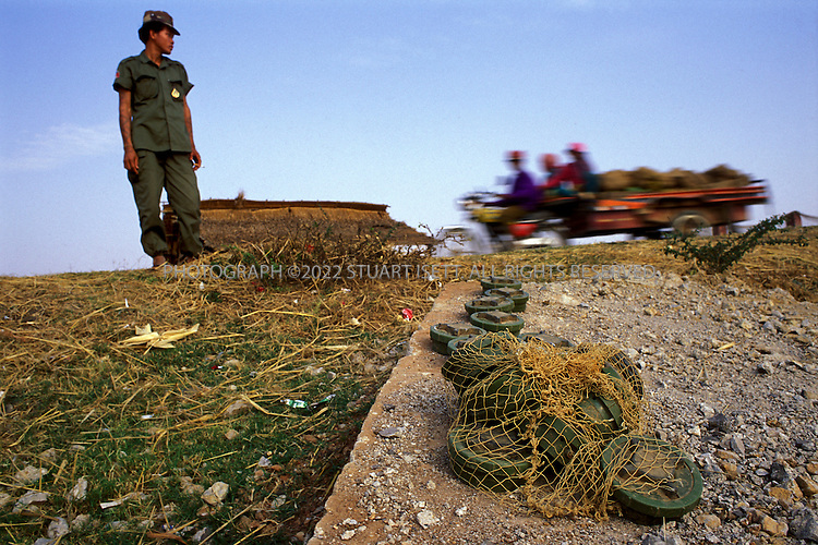Battambang, Cambodia..A Cambodian government soldier stands by the side of a road as he prepares to lay out Chinese made PMN-2 landmines he's carrying in a fishing net....©2003 Stuart Isett All rights reserved