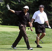 Oak Bluffs, MA - August 24, 2009 -- United States President Barack Obama waves to spectators on Farm Neck Golf Course in Oak Bluffs, Martha's Vineyard down the first fairway with Dr. Eric Whitaker, a long-time friend, of Chicago during a round of golf Monday, August 24, 2009. The President's tee shot landed in the woods. The other players in the foursome were Marvin Nicholson, White House trip director, and Robert Wolf, CEO of UBS. .Credit: Vincent DeWitt - Pool via CNP