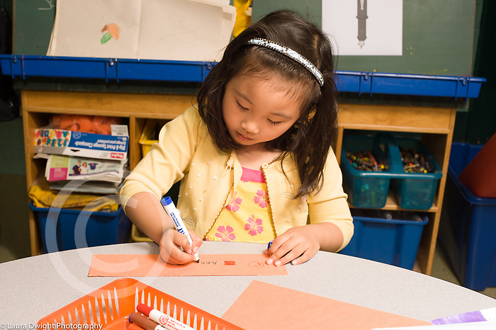 Education Elementary public school Kindergarten girl writing her name on bookmark