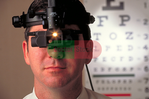 portrait of doctor wearing lighted instrument for examining eyes