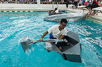 """Hundreds of students from Brooklyn Technical High School take part in the Cardboard Boat Regatta in the school's pool in Brooklyn in New York on Friday, March 1, 2013. As part of Engineering Week the teams of students constructed boats made only of cardboard and duct tape. The team's assigned """"captain"""" piloted their boat from one end of the pool to the other and back in a heat with other boats, hopefully without sinking. The surviving boats were timed and the winners received bragging rights with an award also going to the most spectacular sinking. (© Richard B. Levine)"""