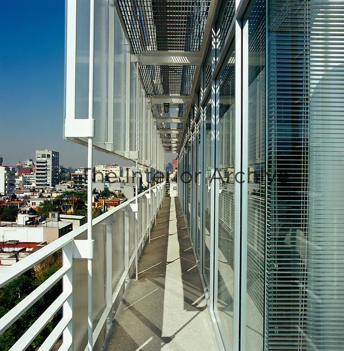 A balcony runs along the side of the building and is lined with layers of polycarbon strips and glass