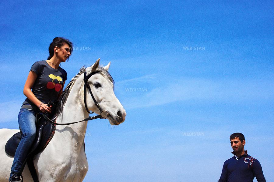 Azerbaijan, Absheron Peninsula, Bine, Hippodrome, April 15, 2012<br /> An Azerbaijani girl learns how to ride a horse at the Hippodrome outside Baku. Horses are culturally very important in Azerbaijan, representing pride and dignity.<br /> <br /> Azerba&iuml;djan, p&eacute;ninsule d'Abcheron, Bina, hippodrome, 15 avril 2012<br /> Une jeune femme azerba&iuml;djanaise apprend &agrave; monter &agrave; cheval dans un hippodrome hors de Bakou. Les chevaux ont une grande importance dans la culture azerba&iuml;djanaise et repr&eacute;sentent la fiert&eacute; et la dignit&eacute;.
