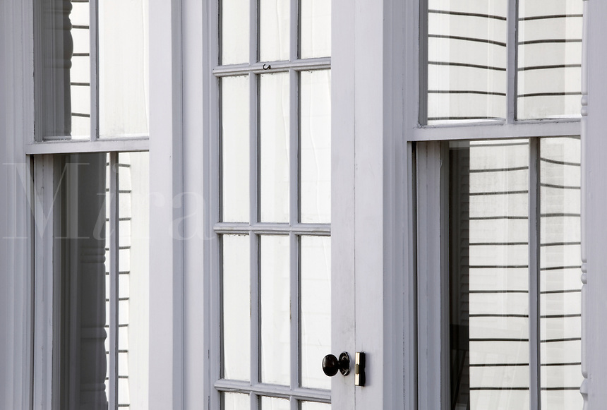 Architectural detail of paned windows reflecting white clapboards. Rockport, Maine.