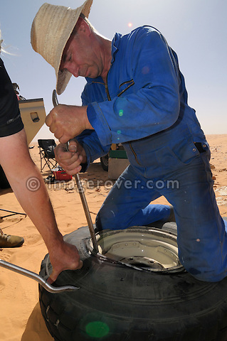 Africa, Tunisia, nr. Tembaine. Siegfried repairing a Land Rover's flat tyre in the desert. --- No releases available, but releases may not be needed for certain uses.