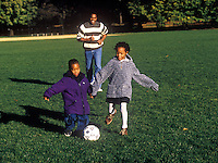 Dad plays soccer with his son and daughter.