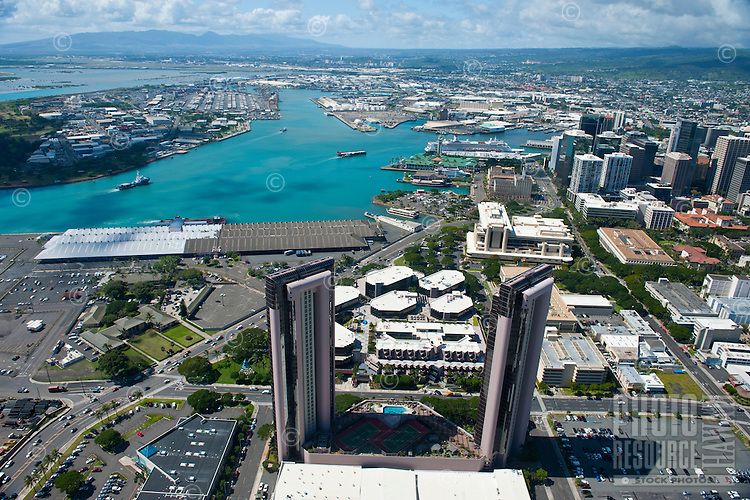 Aerial of downtown Honolulu and harbor with Aloha Tower and cruise ship with WaterfrontTower in foreground and Waianae Mts beyond