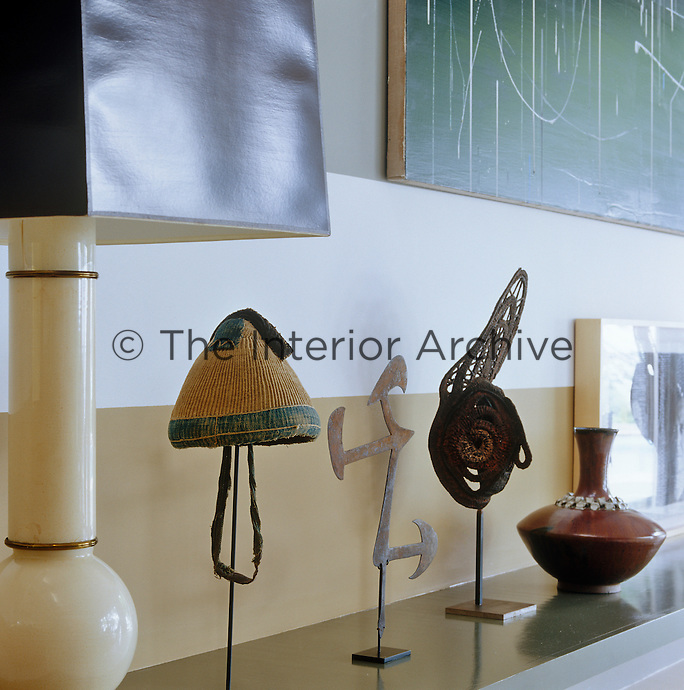 Detail of a collection of ethnic artefacts displayed on a low shelf in the living room