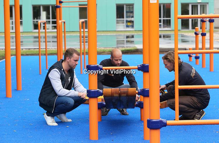 Foto: VidiPhoto<br /> <br /> ARNHEM - Op sportcentrum Papendal bij Arnhem wordt maandag de laatste hand gelegd aan een gloednieuw fitpark dat is over komen waaien uit de VS: streekworkout. Uniek is dat Nederlandse topsporters hier samen met gewone burgers kunnen werken aan hun conditie. Alle andere faciliteiten op Papendal zijn alleen bestemd voor professionele sporters. De &quot;speeltuin voor volwassenen&quot; op Papendal is een afstudeerproject van voormalig topjudoka Dennis Scherpen (l) uit Emmen en moet een voorbeeldfunctie krijgen voor de rest van Nederland. Doel is een streekworkout in alle Nederlandse gemeenten en/of wijken, om zo de fitheid van de Nederlandse bevolking te stimuleren. Streetworkout, een buitenpark met allerlei soorten rekstokken en klimtoestellen, is volgens Scherpen de snelst groeiende trend wereldwijd op dit moment. In Nederland staat het nog in de kinderschoenen. Daar wil de economiestudent nu verandering in brengen. Voor topsporters is het fitpark op Papendal een verrijking en aanvulling op het dagelijkse (kracht)training. In totaal kunnen 20-30 mensen tegelijk trainen op het nieuwe fitpark bij Arnhem. In september wordt het officieel geopend.
