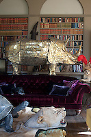 A magnificent sculpture of a gold plated rhinoceros competes with other hunting trophies and a snarling lion skin in the library