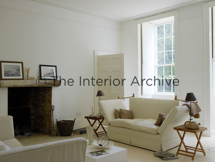 In the living room large curtainless sash windows ensure maximum daylight intensified by the simple white colour scheme