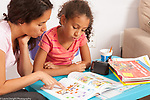 8 year old girl at home Spanish language homework workbook helped by mother