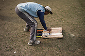 Cricket coach, Balram Singh lays out the cricket bats for young cricketers from the Calcutta Parsee Club during their regular practice session at the maidan in Kolkata, West Bengal, India.