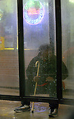 A man waits out of the rain for his bus on North Broad Street on Friday February 6, 2004. photo by jane therese