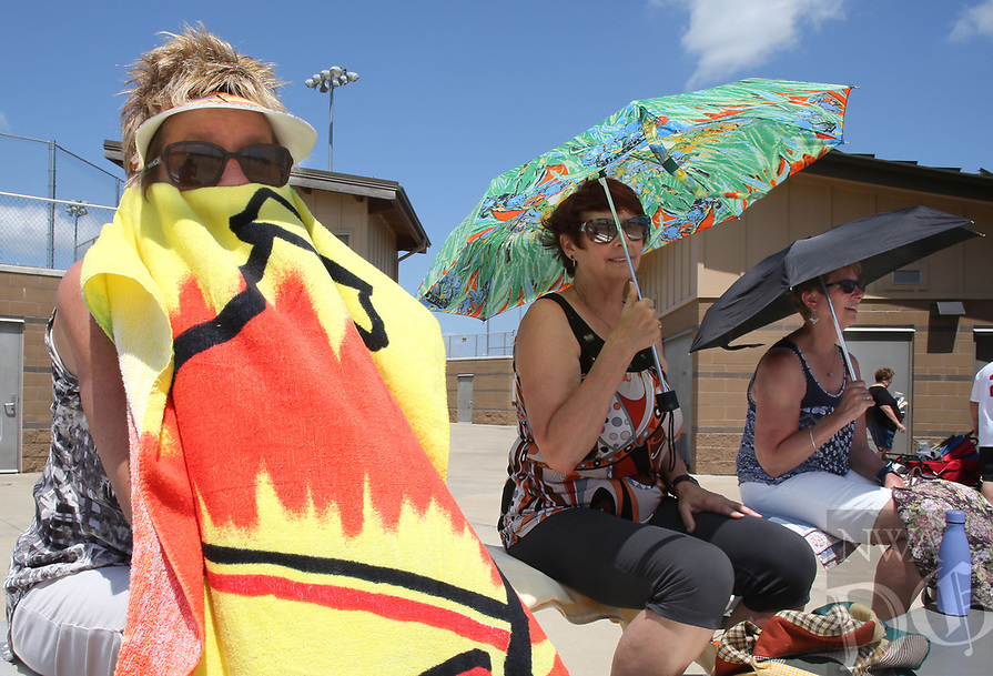 NWA Democrat-Gazette/DAVID GOTTSCHALK   Corinne Paringer (from left), Jean Nelson and Linda Wenzel, all from Wisconsin, shield themselves from the sun as they watch Wednesday, July 12, 2017, the 64 years of age and over mens softball team Hadeland Flooring play at Rogers Regional Sports Park. The team was participating in the Senior Softball USA Midwest Championships 2017 that conclude today (Thursday). The senior age divisions included a variety of age brackets including one comprised of players with ages 75-80 years and above.