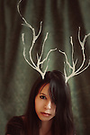Portrait of a young girl with white ink antlers over a dark green backdrop