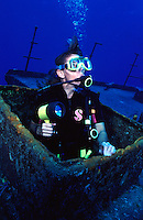 Scuba diver exiting wreck with flashlight, Grand Cayman island.