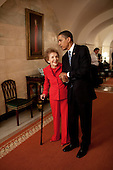 Washington, DC - June 2, 2009 -- United States President Barack Obama and former First Lady Nancy Reagan walk side-by-side through Center Hall in the White House, June 2, 2009. To the left of Mrs. Reagan hangs her official White House portrait as First Lady.  .Mandatory Credit: Pete Souza - White House via CNP