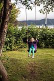 USA, Alaska, Homer, China Poot Bay, Kachemak Bay, playing on the tree swing found on the grounds of the Kachemak Bay Wilderness Lodge