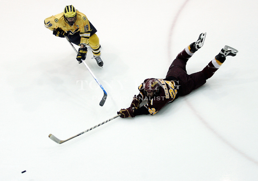 11 March 2006: Ferris State defender Jeremy Scherlinck (24) misses a dive at the puck, followed by Michigan forward Andrew Ebbett (10) during the first period of Ferris State's CCHA quarterfinal-round conference championships game vs No. 14 Michigan, at Yost Ice Arena in Ann Arbor, MI.  Michigan advances to the CCHA Semi-finals winning 3-2.