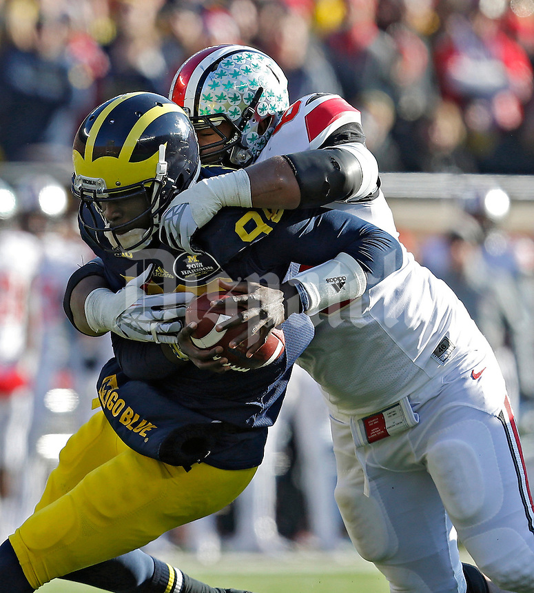 Ohio State Buckeyes defensive lineman Michael Bennett (63) sacks Michigan Wolverines quarterback Devin Gardner (98) in the 3rd quarter of their college football game at Michigan Stadium in Ann Arbor, Michigan on November 30, 2013.  (Dispatch photo by Kyle Robertson)