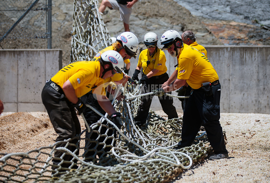 Jun 16, 2018; Bristol, TN, USA; NHRA safety safari rescue crews work to repair the catch net after pro stock driver Tommy Lee (not pictured) crashed into the catch net in the sand trap after his parachutes failed to deploy during qualifying for the Thunder Valley Nationals at Bristol Dragway. Mandatory Credit: Mark J. Rebilas-USA TODAY Sports