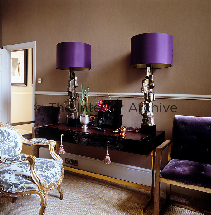 A pair of lamps with cast-bronze bases and purple shades is displayed against rich chocolate linen covered walls in the guest bedroom