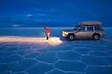 Bolivia, Altiplano, photographer next to 4x4 vehicle in Salar de Uyuni, world's largest salt pan at dusk