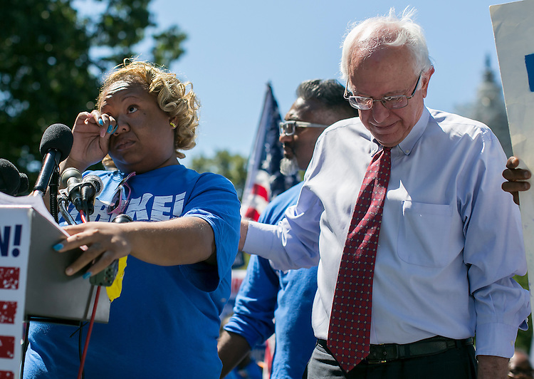 UNITED STATES - JULY 22: Sontia Bailey, a cashier at a cafe inside the U.S. Capitol, wipes a tear as she is comforted by Democratic presidential candidate Sen. Bernie Sanders, I-Vt., as she describes her recent miscarriage and how she was not able to take time off her two jobs during a rally on Capitol Hill in Washington, <br /> Wednesday, July 22, 2015, to push for a raise to the minimum wage to $15 an hour.(Photo By Al Drago/CQ Roll Call)