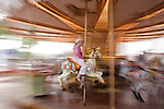 Carousel in Barcelona in motion. Girl in pink hangs on as she goes by