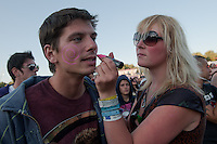 A girl draws symbols on the face of a boy in the audience during Sziget festival held in Budapest, Hungary on August 10, 2011. ATTILA VOLGYI