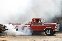 MEGAN DAVIS/MCDONALD COUNTY PRESS Eli Hopkins, of Kansas, burns rubber in his 1978 F150 Ford Ranger as his son, Aaron, is mesmerized by the billowing smoke. Hopkins took to the burn-out area multiple times to spin his wheels during the FORDification Auto Show on Saturday.