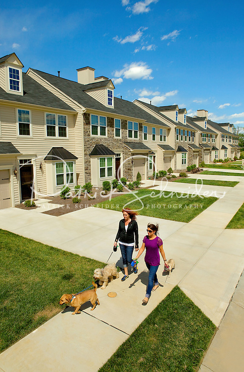 Photography of Charlotte's Berewick community, a planned development located in southwest Charlotte. Image shows residents (model released) walking dogs along a street.